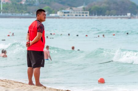 Sanya, China - May 15, 2019: A lifeguard on beach keeps order and safety. In the hands of a whistle to ensure the discipline. T-shirt with the inscription Lifeguard in English and Chinese. Editorial