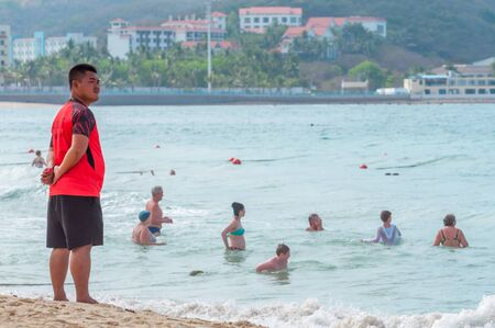Sanya, China - May 15, 2019: A lifeguard on beach keeps order and safety. In the hands of a whistle to ensure the discipline. T-shirt with the inscription Lifeguard in English and Chinese. Stock Photo - 128406793