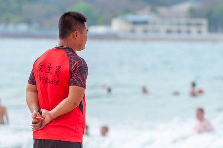 Sanya, China - May 15, 2019: A lifeguard on beach keeps order and safety. In the hands of a whistle to ensure the discipline. T-shirt with the inscription Lifeguard in English and Chinese. Stock Photo - 128406794