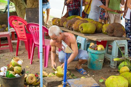 Hainan, China - May 12,2019: A men at a roadside kiosk prepares a coconut with a machete for sale to tourists to drink juice. Stock Photo - 128406792