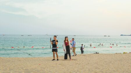Sanya, Hainan, China - May 14, 2019: A group youth on the beach with the help of a smartphone lead live report. Online reporting is a popular activity among Chinese teenagers. Stock Photo - 128406795