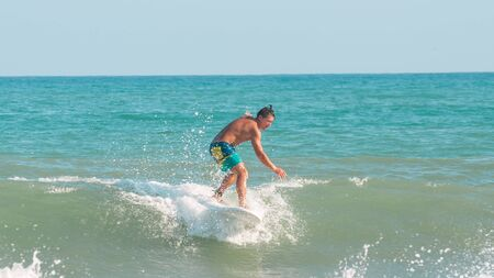 Sanya, hainan, China - May 16, 2019: An unknown young muscular surfer slides beautifully through the azure waves of the South China Sea on a surfboard. Surfing is an extreme beautiful sport.