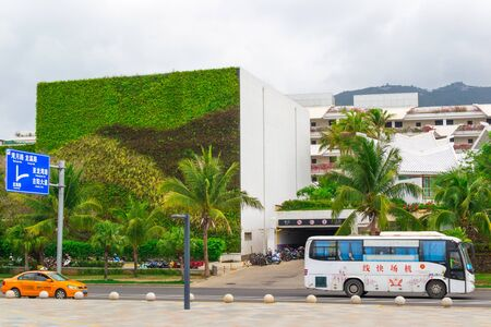 Sanya, Hainan island, China - May 15, 2019: Road traffic. Chinese yellow taxi on the street of Sanya. City landscape. A building with an unusual green facade from living plants