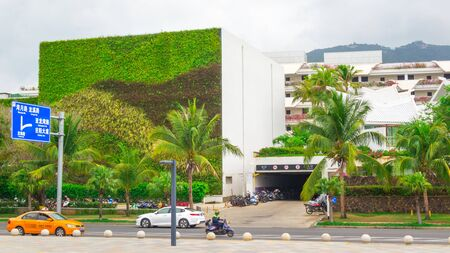 Sanya, Hainan island, China - May 15, 2019: Road traffic. Chinese yellow taxi on the street of Sanya. City landscape. A building with an unusual green facade from living plants Stock Photo - 128406805