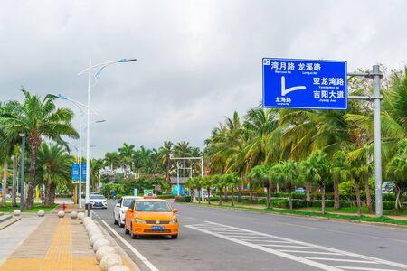 Sanya, Hainan island, China - May 15, 2019: Road traffic. Chinese yellow taxi on the street of Sanya. City landscape