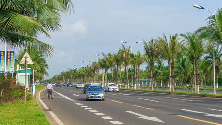 Haikou, Hainan, China - May 12, 2019: Nice view of the roadway. On the dividing line, green tropical palm trees are reinforced with metal structures to protect against frequent typhoons. Stock Photo - 128407025
