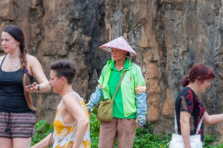 Haikou, Hainan, China - May 12, 2019: Service staff in the Hainan Tropical Wildlife Parc and Botanical Garden. Chinese woman in uniform, working clothes rangers