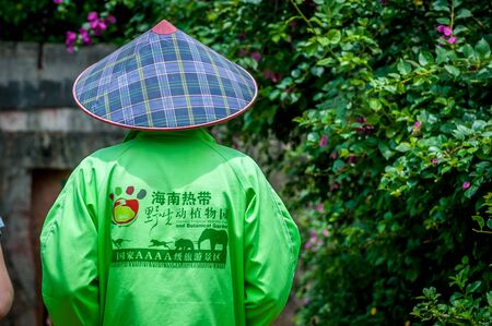 Haikou, Hainan, China - May 12, 2019: Service staff in the Hainan Tropical Wildlife Parc and Botanical Garden. Chinese woman in uniform, working clothes rangers Stock Photo - 128407028