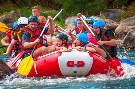Myhia, Ukraine - August 17, 2019: Rafting. A cheerful group of men and women descends on a large inflatable boat on the river. There is a child in the boat. Sincere emotions of happy people. Redakční
