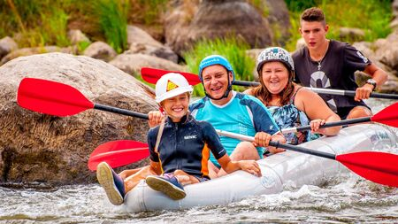 Myhia, Ukraine - August 17, 2019: Rafting. A cheerful friendly family with a child rafting in a rubber inflatable boat on the rapids of a fast river. The concept of a happy family, healthy lifestyle.