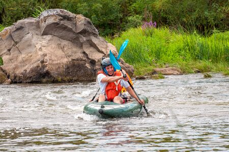Myhiya, Ukraine - August 17, 2019: Rafting trip. Two rowers are rafting down the river in a rubber inflatable boat. The concept of communication of generations, physical activity of the elderly.