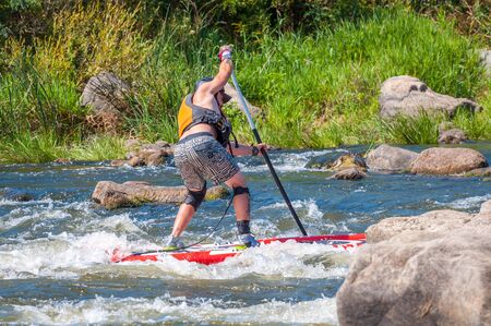 Myhiya, Ukraine - August 17, 2019: Sportsman paddling whitewater river on a inflatable stand up paddle board SUP.