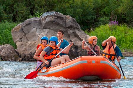 Myhia, Ukraine - August 17, 2019: Rafting. A cheerful group of men and women descends on a large inflatable boat on the river. Sincere emotions of happy people.
