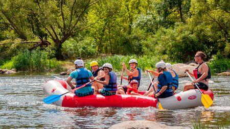 Myhia, Ukraine - August 17, 2019: Rafting. A cheerful group of men and women descends on a large inflatable boat on the river. There is a child in the boat. Sincere emotions of happy people. Editorial