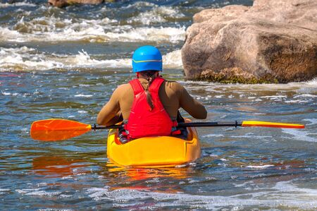 A kayaker with oars in full gear is sitting in a kayak on white water. Back view. Stock Photo