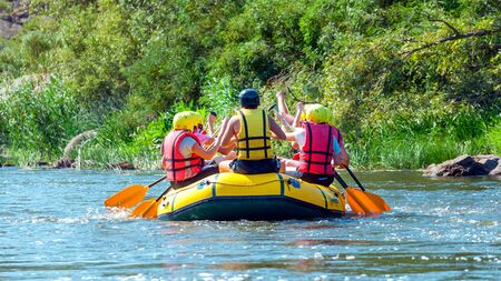 Rafting trip. A group of men and women descends on a large inflatable boat on the river.