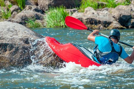 Playboating. A man sitting in a kayak with oars in his hands performs exercises on the water. Kayaking freestyle on whitewater. Eskimo roll.