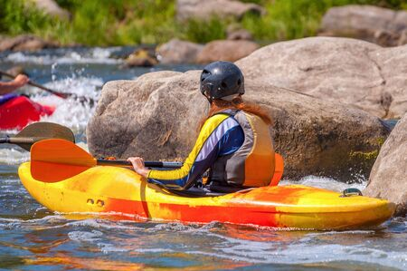 Playboating. A man sitting in a kayak with oars in his hands performs exercises on the water. Kayaking freestyle on whitewater.