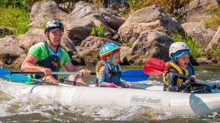 Myhiya, Ukraine - August 17, 2019: Rafting. Father with two children descend on an inflatable boat on the river. Sincere emotions of people. Happy family concept.