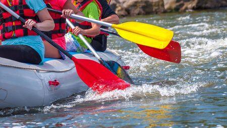 Voyage en rafting. Vue rapprochée des rames avec des éclaboussures d'eau. Les rameurs s'efforcent de surmonter la rivière turbulente. Le concept de travail d'équipe, mode de vie sain. Banque d'images