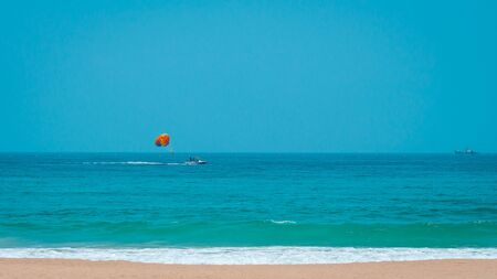 Parasailing is an active form of recreation. The man is towed on a boat and flies with a parachute over the water