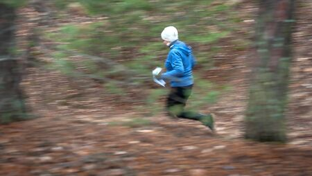 Orienteering. Motion blur. A young girl athlete with a sports card in his hand quickly runs along the orienteering course in the autumn forest. Concept Stockfoto