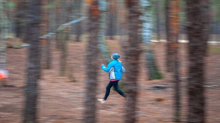 Orienteering. Motion blur. Motion blur. A young girl athlete with a sports card in his hand quickly runs along the distance of orienteering in the autumn forest, approaching a control point. Concept