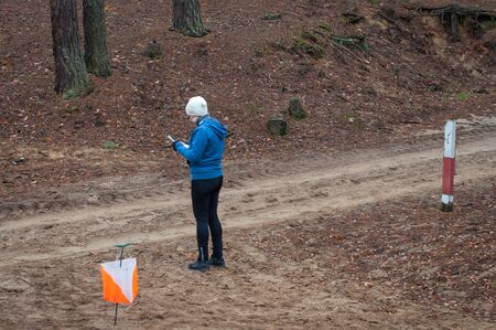 Orienteering. A young girl athlete stands near a checkpoint with a map and determines where to run next