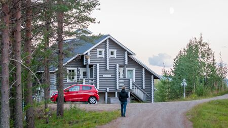 Finland - August 19, 2018. Ukkohalla Ski Resort is located in Central Finland. A cozy picturesque cottage in the middle of an ecologically clean coniferous forest. A red car is parked near the house Éditoriale