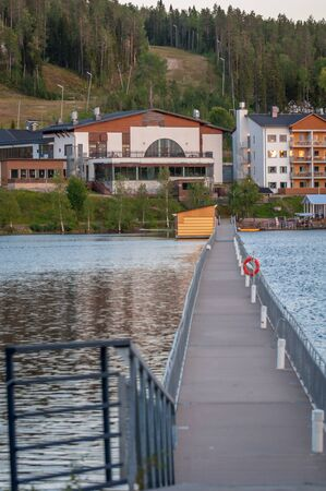 Finland - August 19, 2018. Ukkohalla Ski Resort. The most environmentally friendly air. A lake in the middle of a forest. Cozy picturesque cottages. Footbridge across the lake