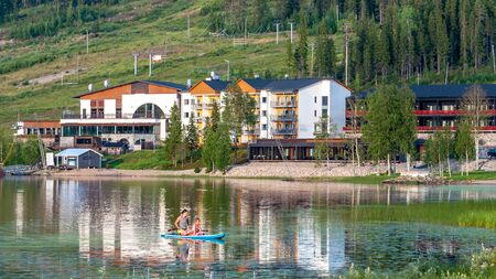 Finland - August 1, 2018. Ukkohalla Ski Resort is located in Central Finland. In summer, water sports and recreation are practiced on the lake. Mom with a child in a rubber boat