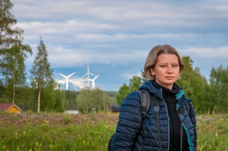 Finland. Woman and electric wind turbine. The concept of clean renewable green energy. Electric wind turbines are an environmentally friendly, harmless technology of the future