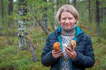 A sincerely smiling woman demonstrates the mushrooms collected in the forest. Picking up fresh organic mushrooms. Finland