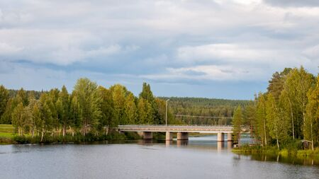Bridge over the pond. A fabulous landscape of a Finnish lake in the midst of a dense Scandinavian green forest. The concept of calm and quiet rest in the most environmentally friendly country