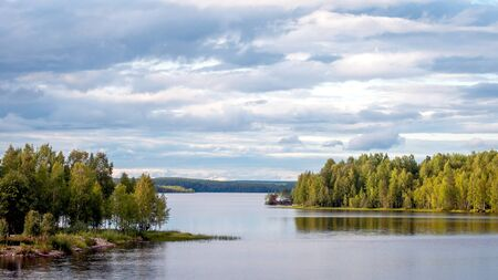 A fabulous landscape of a Finnish lake in the midst of a dense Scandinavian green forest. The concept of calm and quiet rest in the most environmentally friendly country Banque d'images