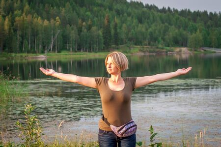 Woman on a background of a lake and a dense green forest with spread arms. Soft lighting at sunset. Banque d'images