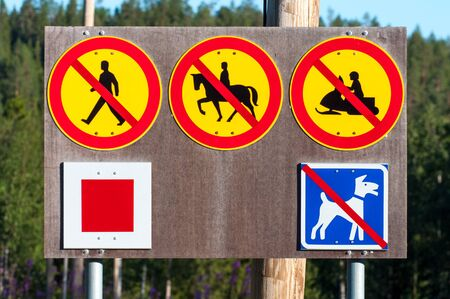 A set of five road signs located on a wooden stand