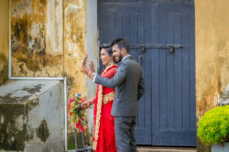 Galle, Sri Lanka - May 28, 2016: The bride and groom are photographed on the street of the old fort. Behind the curtains of a wedding photo shoot of Sri Lankan couples. Éditoriale