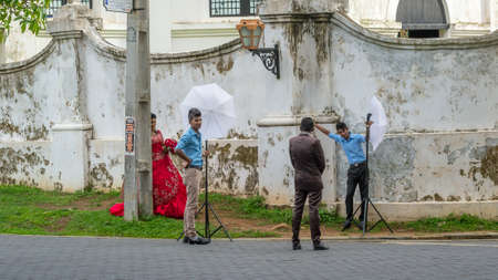 Galle, Sri Lanka - May 28, 2016: The bride and groom are photographed on the street of the old fort. Behind the curtains of a wedding photo shoot of Sri Lankan couples. Sajtókép