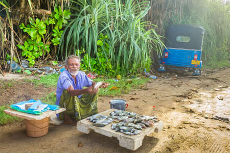Koggala, Sri Lanka - May, 2016: A street seller of fresh fish offers to buy goods from him. Nearby stands his vehicle - tuk-tuk.