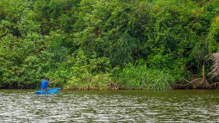 Balapitiya, Madu Ganga river, Sri Lanka - May 29, 2016: A local fisherman in a traditional wooden boat is fishing on the Madu River. He caught a fish.