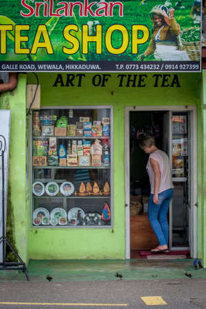 Hikkaduwa, Sri Lanka - May 29, 2016: A small tea shop on Hikaduwa Street. A white woman comes into the store. There are a lot of packages of different tea on the window. Éditoriale