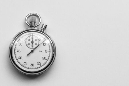 Ancient mechanical stopwatch on a gray background.