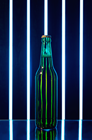 specular: green beer bottle on dark background with bright bands of light and specular reflection