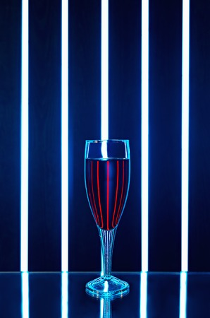 hitech: Glass of red wine on a dark background with reflection and streaks of bright light
