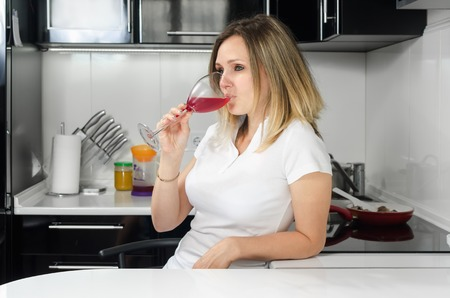 homemaker: successful beautiful girl drinking red wine in the kitchen Stock Photo