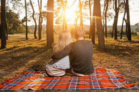 Loving couple sitting embracing on the bedspread during sunset Stock Photo