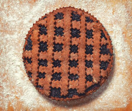 Dark cookie. Stuffed Cocoa Pie. Sprinkle flour on the board. Fresh pie from the oven. Banco de Imagens