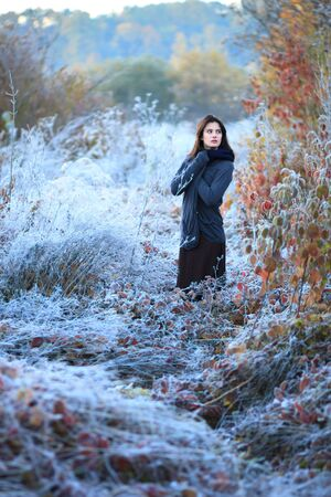 Beautiful sunrise with frost. Portrait of a beautiful girl freezing in the winter forest. Woman in boho style.