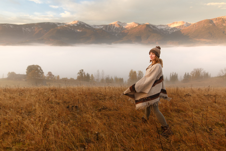 Young woman hiking at mountain peak above clouds and fog Hiker girl wrapping in warm poncho outdoor. Misty mountain. Young girl over the clouds in the valley looking at calm autumn sunrise Stock Photo